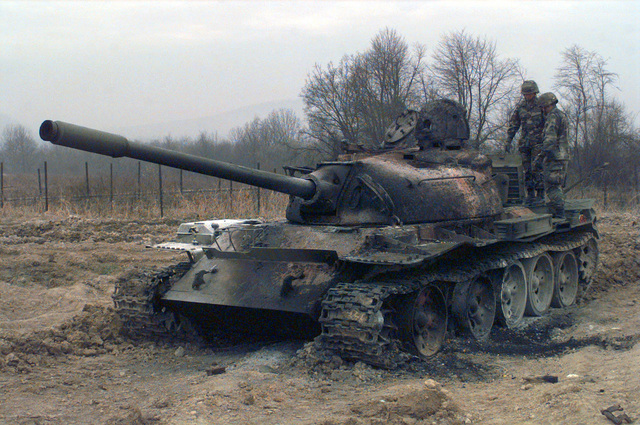 First Lieutenant McCarthy, from the 9th Engineer Battalion, and STAFF Sergeant Duncan, from the 2nd Ordnance (E.O.D.), assess the damages done to the T55 Russian tank, from the day before, on Camp Dobol, Bosnia, during Operation JOINT GUARD. On December 20, 1996, the Implementation Force (IFOR) mission came to a conclusion and the 1ST Infantry Division was selected to continue serving in Bosnia as part of the new Stabilization Force (SFOR). This decision brought to close the peace mission of Operation JOINT ENDEAVOR and has been the beginning for the current operation known as Operation JOINT GUARD. JOINT GUARD will continue to monitor the militaries of the former warring factions and...