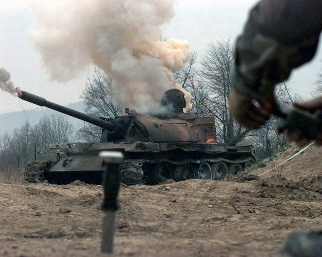 The initial blast of the thermite hand grenades placed in the turret, engine, transmission, and barrel of the T55 Russian tank are being ignited, all at once, by remote using a hand held blasting machine used by the Explosive Ordnance Detachment team on Camp Dobol, Bosnia, during Operation JOINT GUARD. On December 20, 1996, the Implementation Force (IFOR) mission came a conclusion and the 1ST Infantry Division was selected continue serving in Bosnia as part of the new Stabilization Force (SFOR). This decision brought close the peace mission of Operation JOINT ENDEAVOR and has been the beginning for the current operation known as Operation JOINT GUARD. JOINT GUARD will continue...
