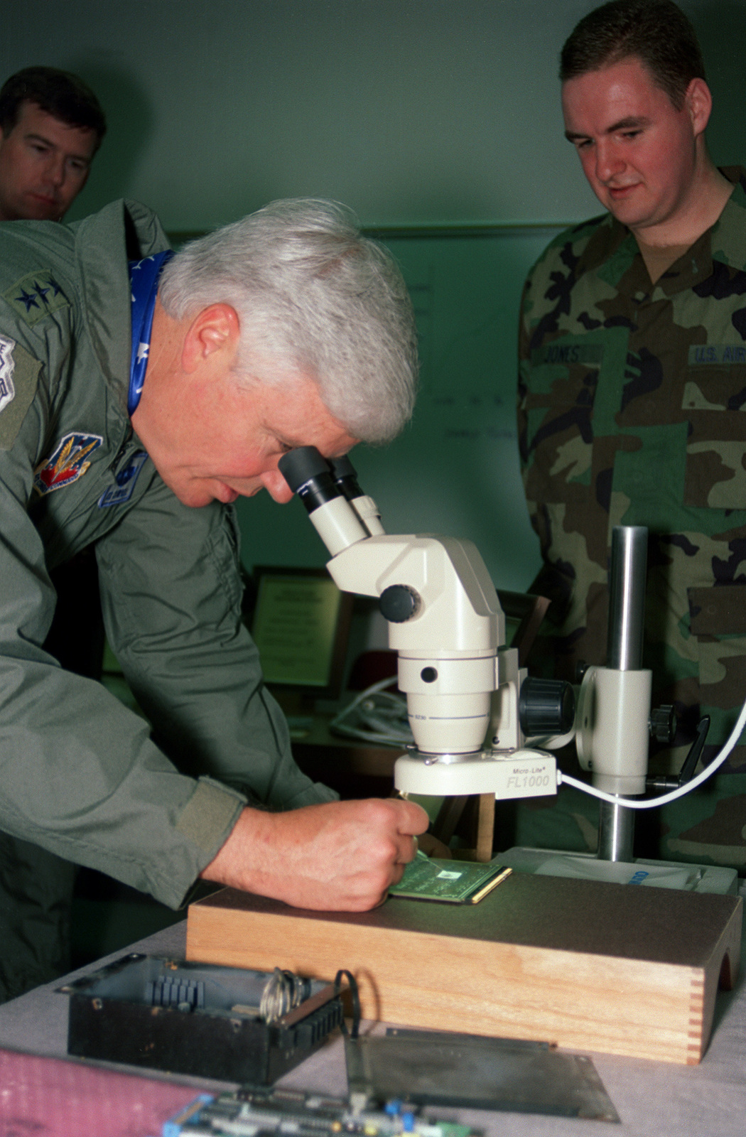 LGEN Frank B. Campbell, 12th Air Force Commander, takes a look at some computer chip repairs through a microscope as SRA Jones (right) observes. The tour took place in the Gold Flag section of the 55th Maintenance Squadron