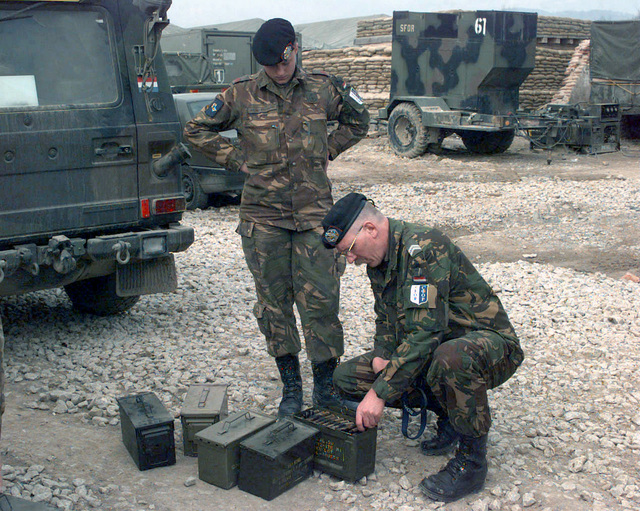 Luxembourg CHIEF Warrant Officer Class Two [WO-2] Hendrik Meijer, Sergeant Major of the101(ML) Mechanized Battalion, inspect 50mm rounds that were unloaded from a Dutch YRP-765 Armored Personnel Carrier, confiscated by SFOR soldiers, on Camp Dobol, Bosnia, during Operation JOINT GUARD. On December 20, 1996, the Implementation Force (IFOR) mission came to a conclusion and the 1ST Infantry Division was selected to continue serving in Bosnia as part of the new Stabilization Force (SFOR). This decision brought to close the peace mission of Operation JOINT ENDEAVOR and has been the beginning for the current operation known as Operation JOINT GUARD. JOINT GUARD will continue to monitor the...