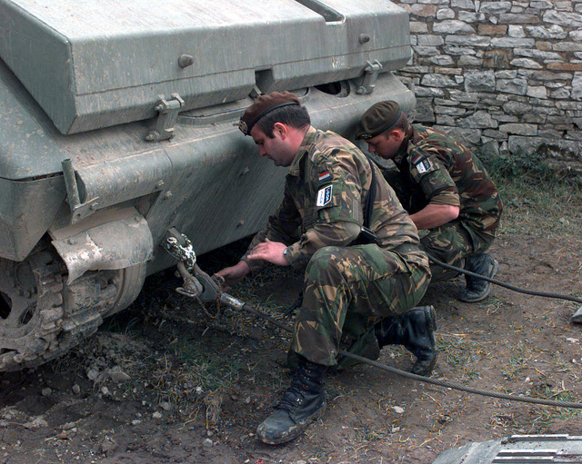 Luxembourg Soldiers, from the 101(ML) Mechanized Battalion, use towing shackles to help pull a YRP-765 Armored Personnel Carrier, confiscated by SFOR soldiers, onto a flat bed truck on Camp Dobol, Bosnia during Operation JOINT ARD. This is the ninth vehicle out of fourteen that has been recovered since Operation Joint Endeavor/Guard. On December 20, 1996, the Implementation Force (IFOR) mission came to a conclusion and the 1ST Infantry Division was selected to continue serving in Bosnia as part of the new Stabilization Force (SFOR). This decision brought to close the peace mission of Operation JOINT ENDEAVOR and has been the beginning for the current operation known as Operation JOINT...