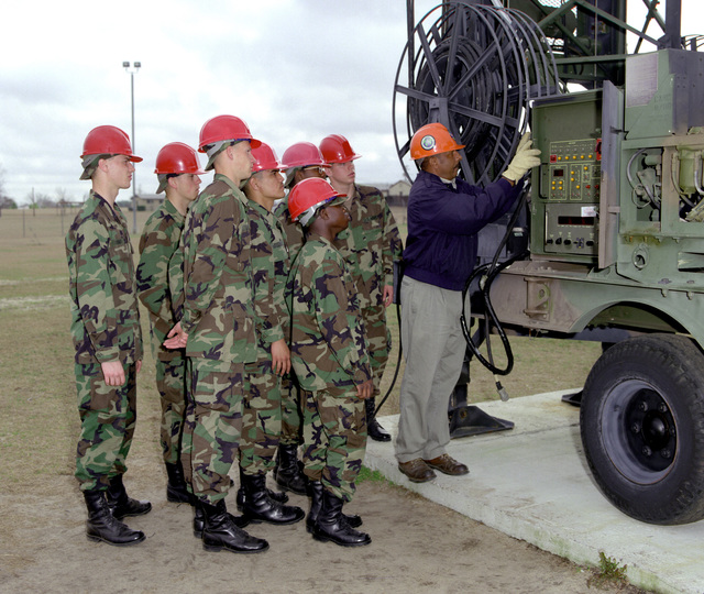 Mr. Lee Taylor, GTE instructor, demonstrates the use of the Azimuth and elevation control box for the Quick Erection Extension Mast (QEEM) antenna AB-1309 to a group of 31R10 students. Antenna is located in the Brems Barrack outdoor training area, GTE MSE Resident School