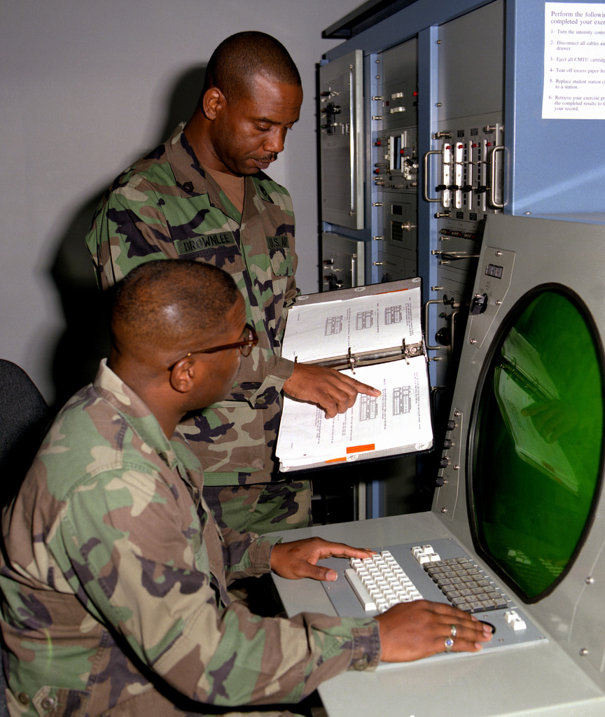 STAFF SGT. Curtis Brownlee is showing STAFF SGT. Calvin Bembry how to perform tutorial exercises on the simulated Node Center Switch (NCS), Enhanced Position Location Reporting System (EPLRS) trainer which is the only one in the world; 31C Course, Vincent Hall