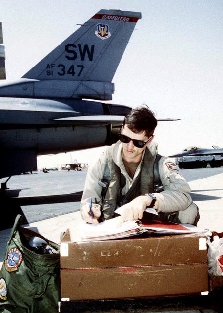 CAPT Tandy Efferson, an F-16 fighting Falcon pilot from Shaw Air Force Base, looks over his preflight check list prior to boarding and taking off on his sortie during Operation SOUTHERN WATCH. SOUTHERN WATCH enforces the United Nations Security Council Resolution 688 that establishes a no-fly zone over Southern Iraq below the 32nd parallel