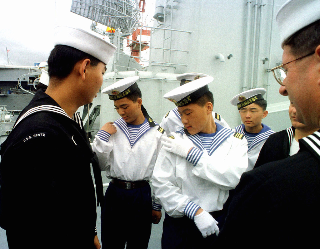 U.S. Navy and Chinese sailors compare uniform insignias while sailors from the People's Republic of China, tour the U.S. Navy Frigate, USS RENTZ (FFG 46). This marks the first time Chinese warships have crossed the Pacific and visited the Continental United States. The Luhu Class Destroyer HARIBING (DDG 112), Luda II Class Destroyer, ZHUHAI (DDG 166), and a supply ship, the Fusu Class, NANYUN (AOR/AK 953) (Chinese vessels not shown), stopped at Naval Station, North Island, San Diego, California