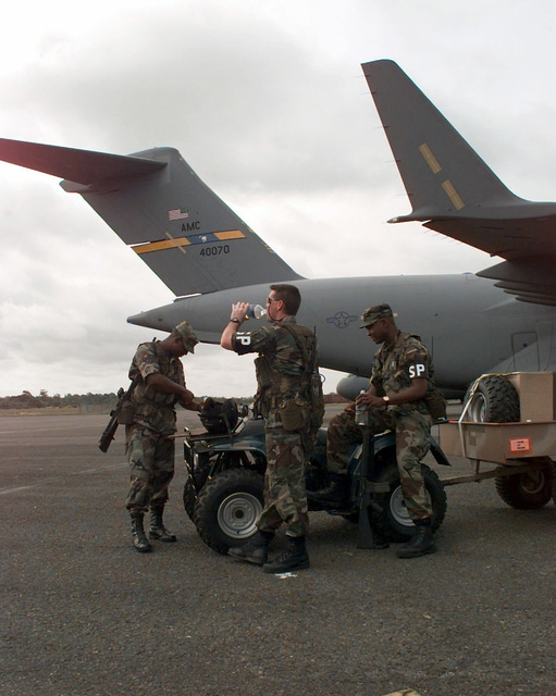 STAFF Sergeant Leo Martin, SENIOR AIRMAN Mike Evans, and SENIOR AIRMAN Robert Herring, all Security Police from the 437th SPS, Charleston Air Force Base, South Carolina, patrol the aircraft with their ATV (all terrain vehicle) at the Libreville International Airport, Gabon, prior to missions for Operation PHOENIX GAUNTLET. PHOENIX GAUNTLET deployed enabling forces as part of contingency planning to prepare for a possible evacuation of Americans from Zaire, gripped in a civil war