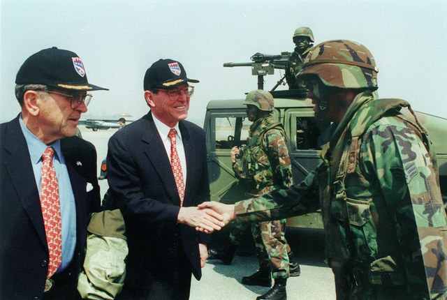 Senators Ted Stevens (R-AK) and Pete V. Dominici (R-NM) talk with security police during Air Base Defense operations. A soldier mans a .50 caliber machine gun on top of a High-Mobility Multipurpose Wheeled Vehicle (HMMWV) in the background