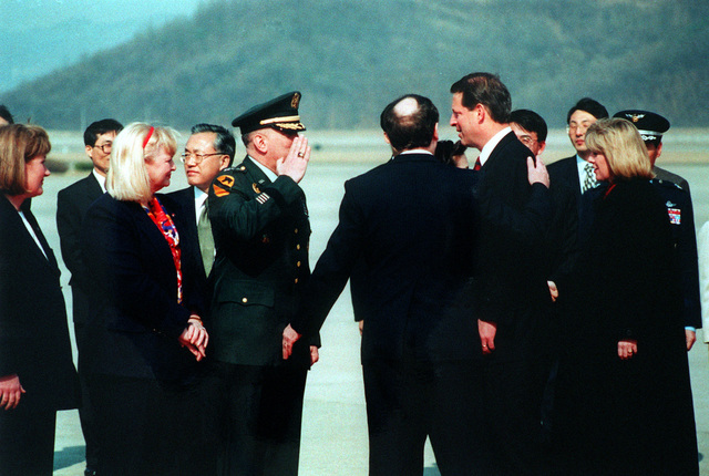 GEN. John H. Tilelli, Jr., salutes Vice-President Al Gore as he arrives at K-16 Air Base Seoul. Each gentlemen is accompanied by his wife