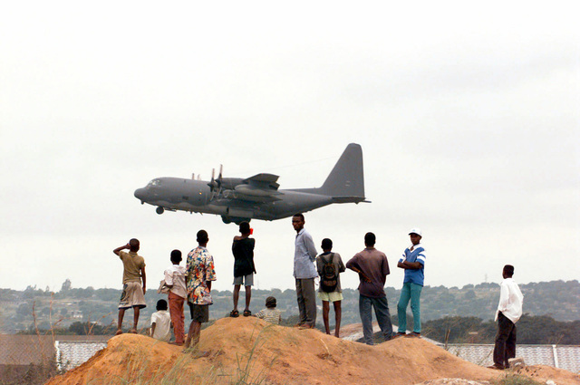 Host Nation locals watch from a hill outside the perimeter fence as a US Air Force Special Operations Command MC-130H Combat Talon II takes-off from Brazzaville Airport, Republic of Congo. The MC-130H was participating in PHOENIX GAUNTLET. PHOENIX GAUNTLET deployed enabling forces as part of contingency planning to prepare for a possible evacuation of Americans from Zaire, gripped in a civil war