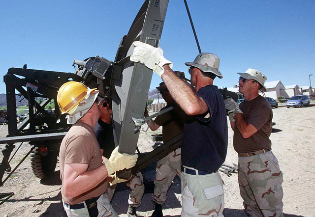 Airmen assigned to the 225th Combat Communications Squadron, Martin Air National Guard Station, Gadson, Alabama, attach a dish to a TRAC-170 Wideband System. The 225th arrived today at Logan Heights in El Paso, Texas. When the TRAC-170 is operational, it will provide communications links for FORSCOM (Forces Command) during ROVING SANDS '97. ROVING SANDS is a multinational effort and is the largest military exercise on United States soil that allows training in a joint environment to hone command and control procedures and integrate new systems in Theater and Air Missile Defense