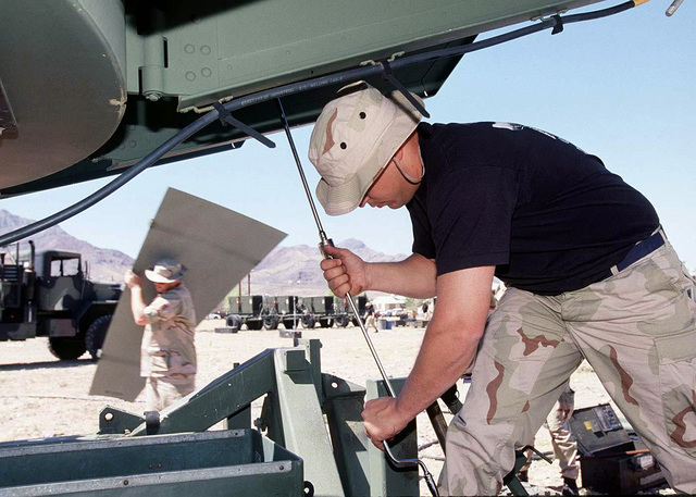 An airman assigned to the 225th Combat Communications Squadron, Martin Air National Guard Station, Gadson, Alabama, tightens down bolts that hold the reflector sections for the Ground Mobile Forces (GMF) Satellite Terminal in place. The 225th arrived today at Logan Heights in El Paso, Texas. When operational, the GMF will provide communications links for FORSCOM (Forces Command) during ROVING SANDS '97. ROVING SANDS is a multinational effort and is the largest military exercise on United States soil that allows training in a joint environment to hone command and control procedures and integrate new systems in Theater and Air Missile Defense