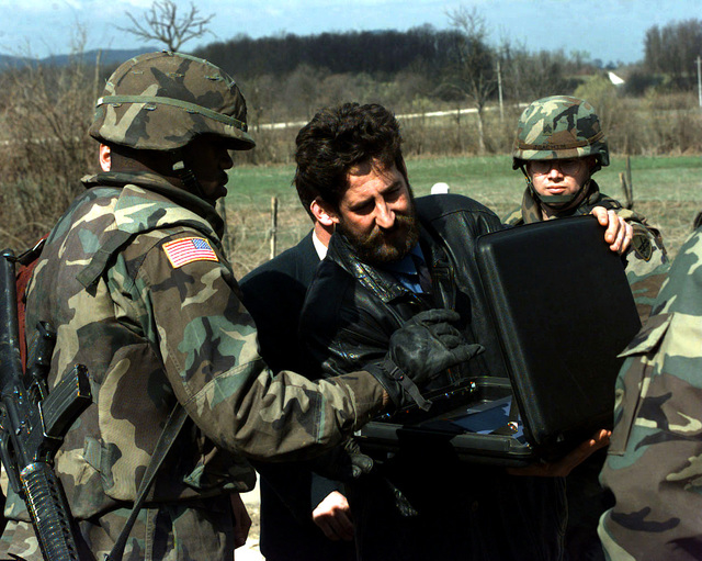 US Army, Private First Class (PFC) Terry Dunavent, Delta Company , 1ST Battalion, 41st Infantry, Fort Riley, Kansas, searches the briefcase of a businessman for weapons at the front gate of checkpoint Sierra 10 before the civilian can enter for an economic meeting. Bosnia-Herzegovina, Operation JOINT GUARD, 8 April 1997