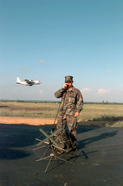 US Marine Corps Corporal Joseph Calebro uses an AN/PSC-3 Satellite Communications Radio on the tarmac at Pointe Noire, Congo, as a VMGR-252 KC-130R takes-off in the background. Corporal Calebro is attached to VMGR-252 (Detachment Bravo) to provide KC-130 Hercules aircraft secure communications while deployed during PHOENIX GAUNTLET. PHOENIX GAUNTLET deployed enabling forces as part of contingency planning to prepare for a possible evacuation of Americans from Zaire, gripped in a civil war