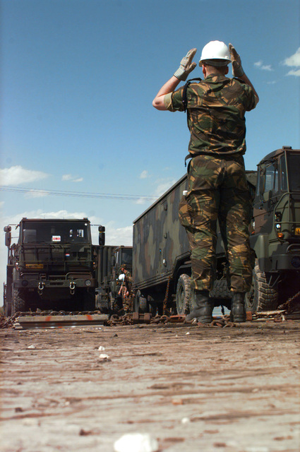 Corporal J. Van der Zouw marshals one of the trucks off the train. The trucks will be used in support of the world's largest joint service, multi-national tactical air operations exercise