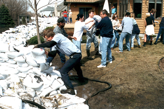 [Severe Storms/Flooding] Fargo, ND, 04/10/1997 -- Residents build up a sandbag levee as residents and volunteers fight the rising waters of the Red River. FEMA/David Saville