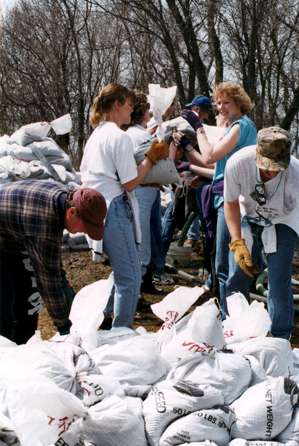 [Severe Storms/Flooding] Fargo, ND, 04/15/1997 -- Residents build up levees with sandbags as residents and volunteers prepare for the rising waters of the Red River of the North.  FEMA/David Saville