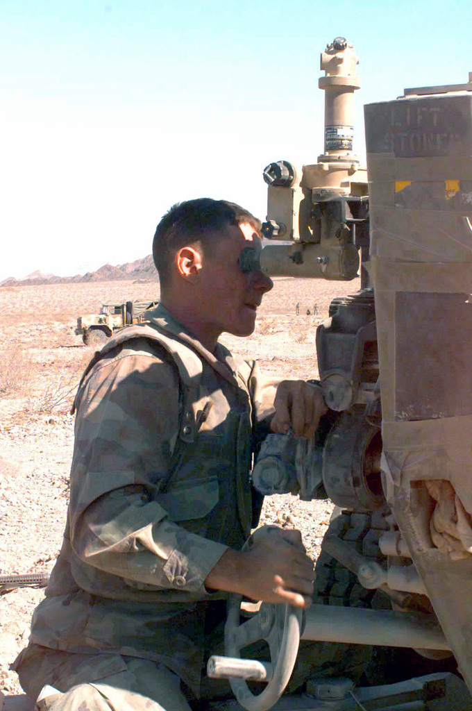 Corporal M. T. Chastain, a cannoneer attached to Golf Battery, 2nd Battalion, 10th Marines, Sites in on the proper grid coordinates for the fire mission on the M198 155mm Medium Towed Howitzer during COMBINED ARMS Exercise (CAX) 5-97. CAX 5/6-97 is a MAGTF (Marine Air Ground Task Force) exercise being conducted at MCAGCC (Marine Corps Air Ground Center), 29 Palms, California. The command element for this exercise is MAGTF-6, built around the 6th Marine Regiment, 2d Marine Division, Camp Lejeune, North Carolina. Many commands from the II MEF (Marine Expeditionary Force) have sent units to this desert warfare exercise, to fill key billets in the Ground Element (GCE), Air...