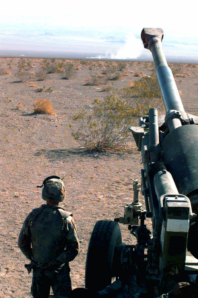 Corporal M. T. Chastain an artilleryman attached to Golf Battery, 2d Battalion, 10th Marines, observers the impact of a 155mm white phosphorus round fired from a M198 Medium Towed Howitzer during COMBINED ARMS Exercise (CAX) 5-97. CAX 5/6-97 is a MAGTF (Marine Air Ground Task Force) exercise being conducted at MCAGCC (Marine Corps Air Ground Combat Center), 29 Palms, California. The command element for this exercise is MAGTF-6, built around the 6th Marine Regiment, 2d Marine Division, Camp Lejeune, North Carolina. Many commands from the II MEF (Marine Expeditionary Force) have sent units to this desert warfare exercise, to fill key billets in the Ground Combat ment (GCE), Air Combat...