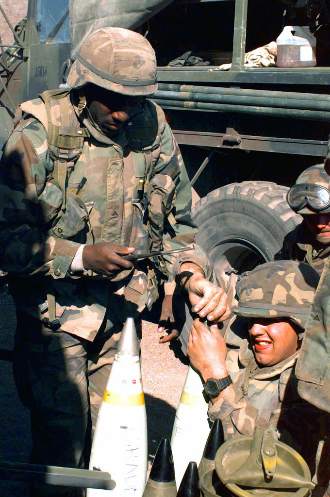 Sergeant M. E. Jones and Corporal L. H. Gaskin, artillerymen attached to Golf Battery, 2d Battalion 10th Marines, check the fuse on a 155 mm white phosphorus round used in a M198 155mm Medium Towed Howitzer during COMBINED ARMS Exercise (CAX) 5-97. CAX 5/6-97 is a MAGTF (Marine Air Ground Task Force) exercise being conducted At MCAGCC (Marine Corps Air Ground Combat Center), 29 Palms, California. The command element for this exercise is MAGTF-6, built around the 6th Marine Regiment, 2d Marine Division, Camp Lejeune, North Carolina. Many commands from the II MEF (Marine Expeditionary Force) have sent units to this desert warfare exercise, to fill key billets in the Ground Combat Element...