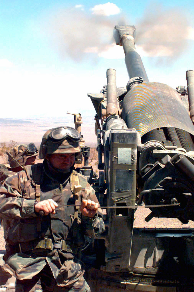 Sergeant T. M. Dale Jr., a combat photographer with 2d Marine Division Combat Camera Unit, fires a round from the M198 155mm Medium Towed Howitzer during COMBINED ARMS Exercise (CAX) 5-97. CAX 5/6-97 is a MAGTF (Marine Air Ground Task Force) exercise being conducted At MCAGCC (Marine Corps Air Ground Combat Center), 29 Palms, California. The command element for this exercise is MAGTF-6, built around the 6th Marine Regiment, 2d Marine Division, Camp Lejeune, North Carolina. Many commands from the II MEF (Marine Expeditionary Force) have sent units to this desert warfare exercise, to fill key billets in the Ground Combat Element (GCE), Air Combat Element (ACE) and the Combat Service...