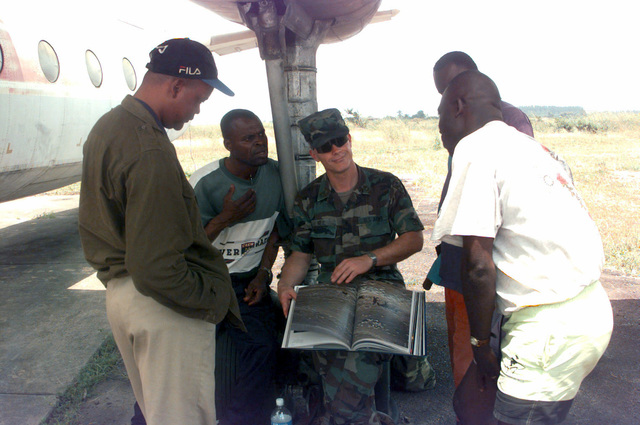 Under the wing of a non-operational Congolese AN-24 transport, United States Army Sergeant (SGT) First Class Chris Neil, shows the book 'A Day in the Life of America' to fascinated civilians at the Maya Maya Aeroport located in Brazzaville, Congo. From left to right are Bianco Capo, Alain Muoukani, SGT 1ST Class Chris Neil, Thierry Gongala, and Lekoubi Corneille
