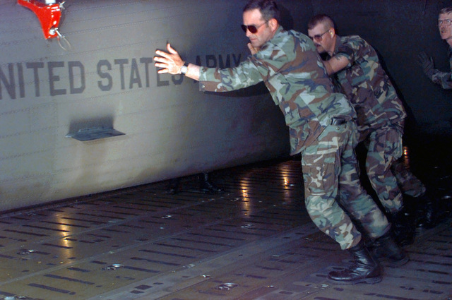 Members of the 147th Aviation Battalion of Madison, Wisconsin, help move a UH-60 Blackhawk helicopter to the off ramp of the C-5 Galaxy where it will be lowered onto the flight line to join the rest of its team at Biggs Army Airfield, El Paso, Texas, to be used in support of ROVING SANDS '97. ROVING SANDS is a multinational effort and is the largest military exercise on United States soil that allows training in a joint environment to hone command and control procedures and integrate new systems in Theater and Air Missile Defense
