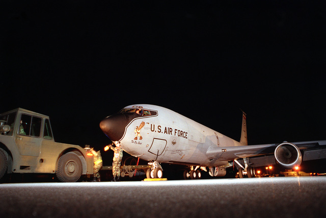 Nighttime view as a KC-135R tanker, assigned to the 100th Air Refueling Wing, as it is pushed into its parking space on the flight line by an aircraft tug