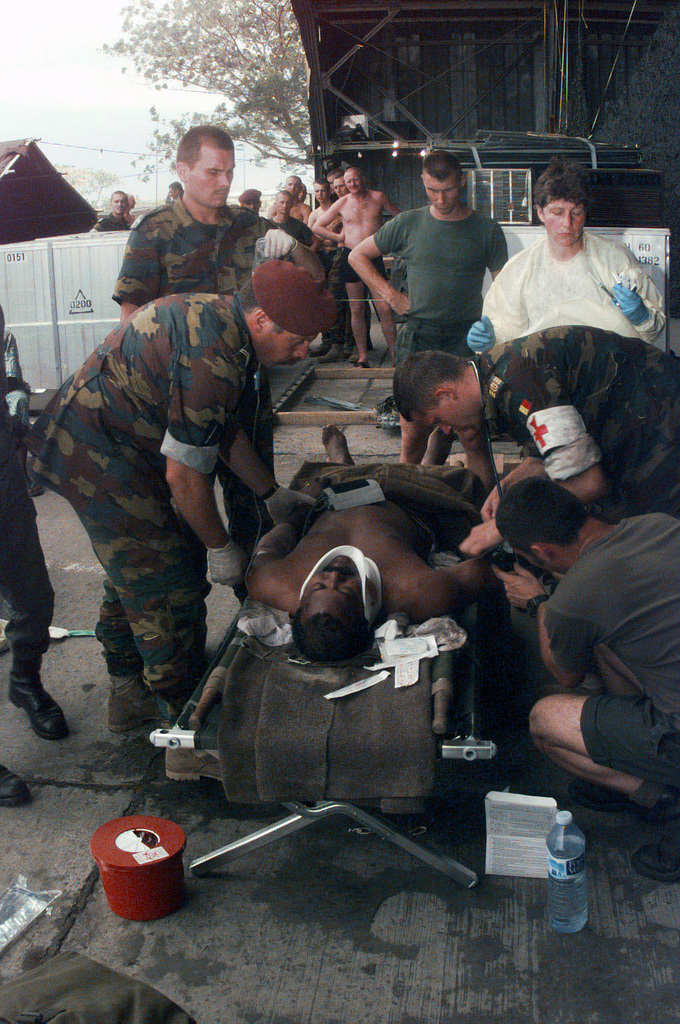 United States Air Force and Belgium Army medical staff work on a Angolan patient injured in the crash of his AN-24 transport on take-off from the Brazzaville, Congo airport. The patient was taken from the crash site at the end of the runway to the medical facility located in a Congolese hangar near the middle of the runway which was in place in support of PHOENIX GAUNTLET. PHOENIX GAUNTLET deployed enabling forces as part of contingency planning to prepare for a possible evacuation of Americans from Zaire, gripped in a civil war