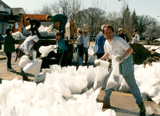 [Severe Storms/Flooding] Fargo, ND, 04/15/1997 -- Newly filled sandbags are moved around by truck to a levee that's being raised.  The entire community is working with volunteers to protect neighborhoods from the rising waters of the Red River of the North.  FEMA/David Saville