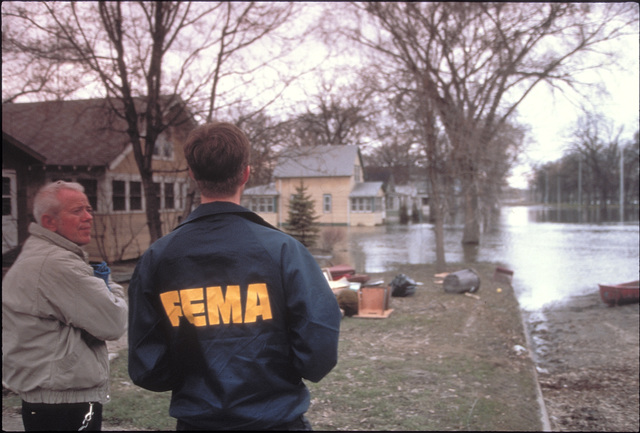 [Severe Storms/Flooding] Grand Forks, ND, April 15, 1997 - A FEMA worker talks to a resident about the flooding damage to this neighborhood. The men are waiting for the Red River waters recede.  FEMA/Michael Rieger