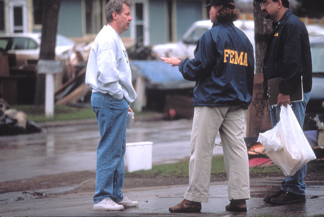 [Severe Storms/Flooding] Grand Forks, ND, April 15, 1997 - FEMA Community Relations members talk to a resident about FEMA recovery help. FEMA CR workers canvas once flooded neighborhoods talking with residents and giving recovery information and contact phone numbers.  FEMA/Mike Rieger