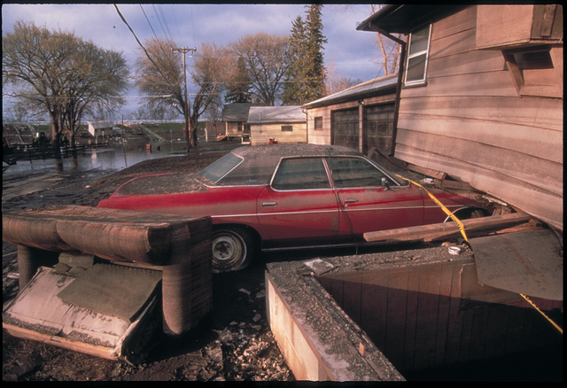 [Severe Storms/Flooding] Grand Forks, ND, April 15, 1997 - This house was lifted by flood waters and came to rest on a car. Houses were moved off their foundations as the Red River flood waters came though Grand Forks. FEMA/Michael Rieger
