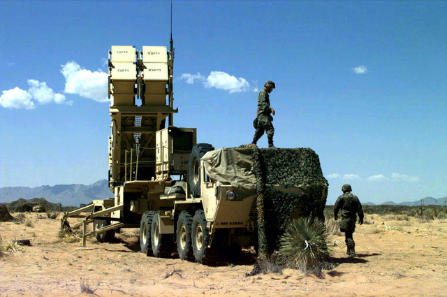 US Army SPECIALIST (SPC) Guerra and Private First Class (PFC) Sabree, A Battery, 5th Battalion, 52nd Air Defense Artillery, 11th ADA Brigade, prepare a four canister launcher, on an M-109 trailer, for an MIM-104 Patriot Missile Launch Drill at Base Camp McGregor Missile Range, Fort Bliss, Texas, during Exercise ROVING SANDS '97, 15 April 1997