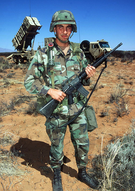 SPECIALIST Matthew Covington, Alpha 5-52 Air Defense Artillery Brigade, Fort Bliss, Texas, stands guard in front of a Patriot missile battery. The Patriot missile system will be used by the Blue Forces to defend against Red Forces' air attacks during this, the world's largest joint service, multi-national tactical air operations exercise.(Duplicate image, see also DD-SD-01-04259 or search 970416-F-2555H-101)