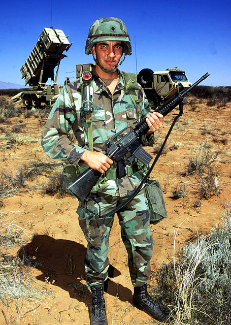 US Army, SPECIALIST (SPC) Matthew Covington, Alpha Battery, 5th Battalion, 52nd Air Defense Artillery, 11th ADA Brigade, Fort Bliss, El Paso, Texas, stands guard with an M-16 rifle in front of an MIM-104 Patriot missile battery. The Patriot missile system will be used by the blue forces to to defend against red forces' air attacks during Exercise ROVING SANDS '97, 16 April 1997. (Duplicate image, see also DF-SD-99-00832 or search 970416-F-2555H-101 )