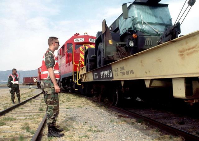 SPECIALIST Winkelmann, US Army, helps guide a locomotive to the depot at Biggs Army Airfield, El Paso, Texas. The train is loaded with military vehicles to be used in support of helicopter operations during ROVING SANDS '97. ROVING SANDS is a multinational effort and is the largest military exercise on United States soil that allows training in a joint environment to hone command and control procedures and integrate new systems in Theater and Air Missile Defense