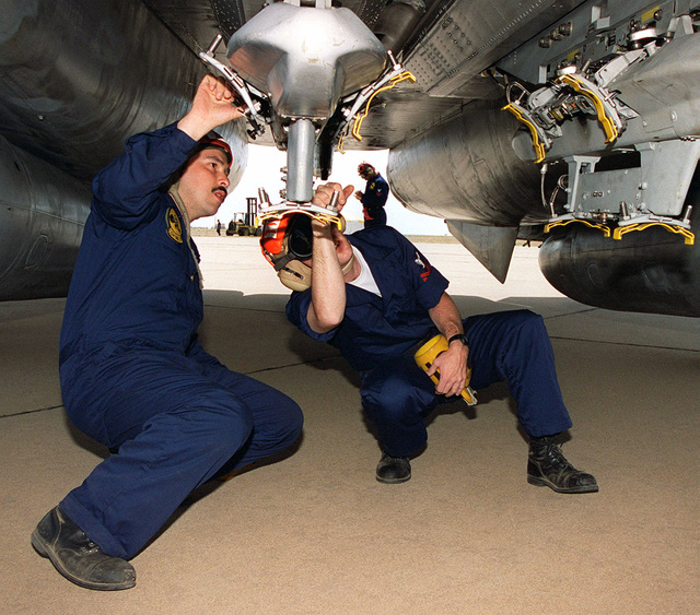 Navy AIRMAN, AO2 John Escarcida and AO2 Scott Beatty of Fighter Squadron 143, Naval Air Station Oceana, Virginia, check the bomb holders on an F-14 Tomcat. The sailors and aircraft are part of the Command Air Group (CAG) operations deployed to support the world's largest joint service, multi-national tactical air operations exercise