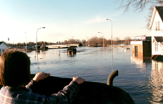 [Severe Storms/Flooding] East Grand Forks, MN, 04/18/97 -- A resident watches a National Guard truck move through the streets of East Grand Forks evacuating residents as flood waters rise.  FEMA/David Saville
