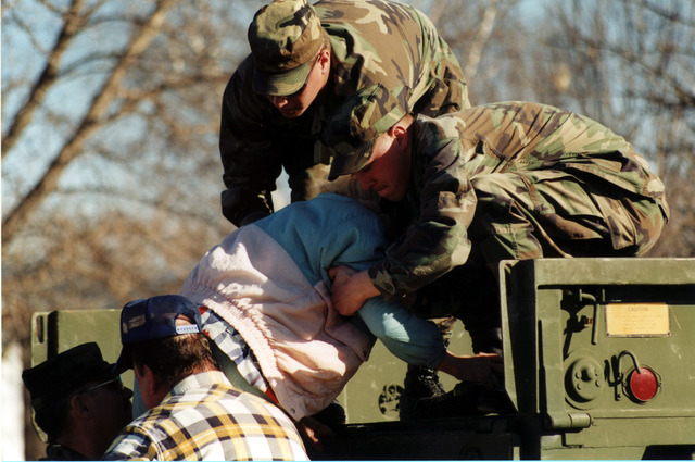 [Severe Storms/Flooding] East Grand Forks, MN, 04/18/97 -- National Guardsmen help an elderly lady into a truck as East Grand Forks is evacuated. FEMA/David Saville