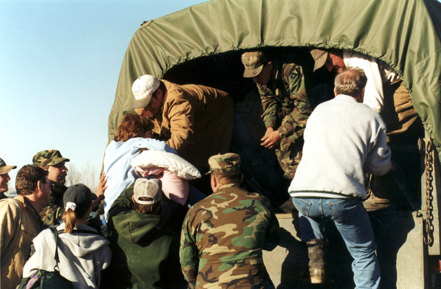 [Severe Storms/Flooding] East Grand Forks, MN, 04/18/97 -- Residents of East Grand Forks are helped into National Guard trucks as the city is evacuated. FEMA/David Saville