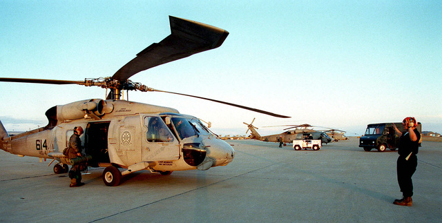 A helicopter maintenance man signals the SH-60 Seahawk helicopter pilot as the rest of the crew removes their gear after a familiarization flight over the Alamogordo bombing range. The helicopter and ground crew are from the Helicopter Anti-Submarine Squadron, North Island, California, and are in New Mexico participating in ROVING SANDS '97. The helicopters are participating as part of the Red forces for the exercise. ROVING SANDS is a multinational effort and is the largest military exercise on United States soil that allows training in a joint environment to hone command and control procedures and integrate new systems in Theater and Air Missile Defense