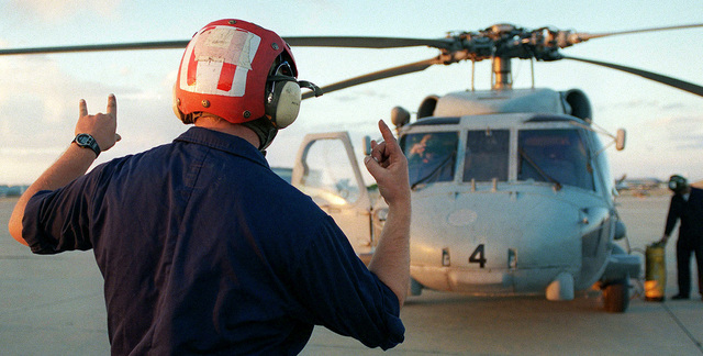A helicopter maintenance man signals the SH-60 Seahawk helicopter pilot during engine shut down after a familiarization flight over the Alamogordo bombing range. The helicopter and ground crew are from the Helicopter Anti-Submarine Squadron, North Island, California, and are in New Mexico participating in ROVING SANDS '97. The helicopters are participating as part of the Red forces for the exercise. ROVING SANDS is a multinational effort and is the largest military exercise on United States soil that allows training in a joint environment to hone command and control procedures and integrate new systems in Theater and Air Missile Defense