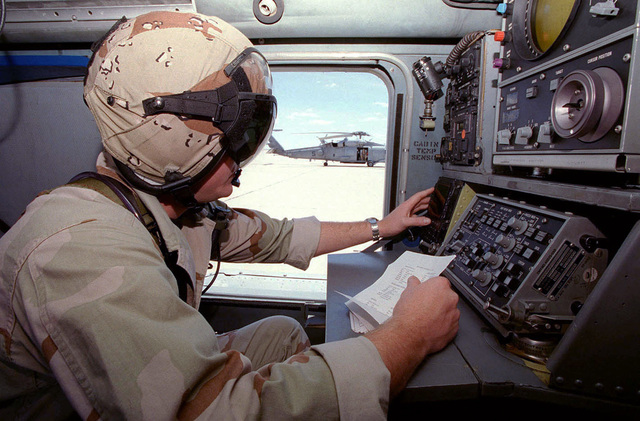 Crew chief, AWC Paul Schenk, checks out the Control Display Unit (CDU) of the Navy SH-60 Black Hawk (Blackhawk) helicopter, another SH-60 is in the background, before taking off on a familiarization flight. Assigned to the Helicopter Anti-Submarine Squadron, North Island, California, the SH-60's aircraft and crew's mission, during the world's largest joint service, multi-national tactical air operations exercise includes a search for scud missile sites on the Alamogordo bombing range