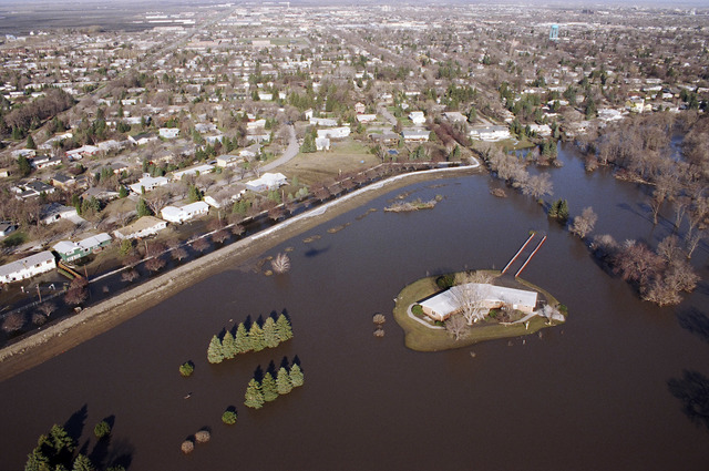 [Severe Storms/Flooding] Grand Forks, ND, April, 1997 -- Aerial view of a flooded property with a house and it's immediate lawn like an island in Grand Forks. FEMA/Michael Rieger