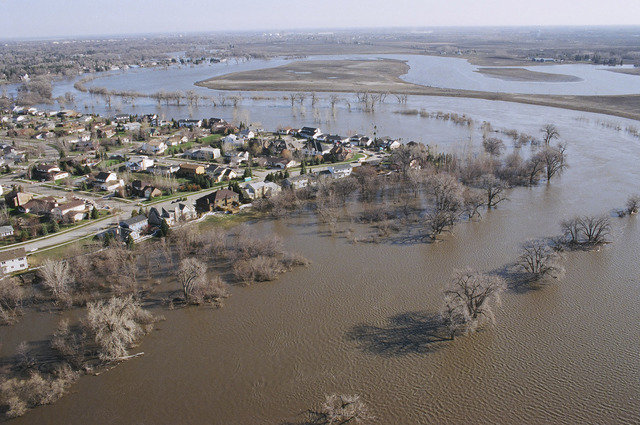 [Severe Storms/Flooding] Grand Forks, ND, April, 1997 -- Aerial view of a sandbagged neighborhood in Grand Forks with the flooded Red River winding around the area.  FEMA/Michael Rieger