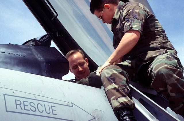 AIRMAN First Class Edward Pogue, 523rd Fighter Squadron, Cannon Air Force Base, NEW MEXICO, helps Captain Tim Coulon snap his harness into place in preparation for a F-16 Fighting Falcon flight. The 523rd Fighter Squadron is supporting ROVING SANDS '97; a joint service exercise designed to improve air defense capabilities