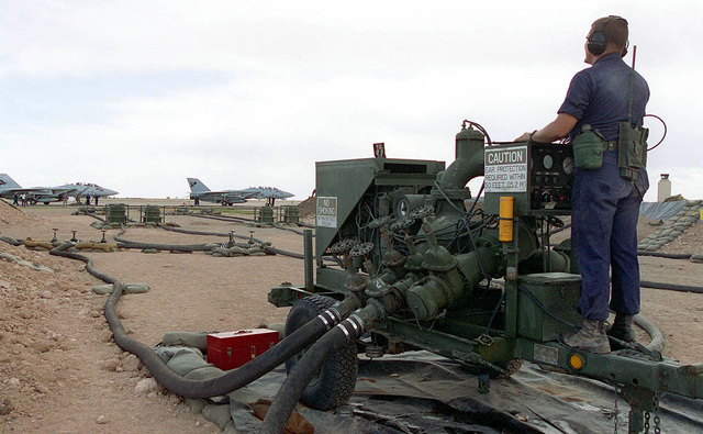 "LCPL Terry Cook, a bulk fuel specialist with the 273rd Marine Wing Support Squadron, Buford, South Carolina, monitors a fuel pump while the aircraft are being ""hot"" refueled. Most of the fighters operating at Roswell Industrial Air Center are being refueled with the engines running during world's largest joint service, multi-national tactical air operations exercise"