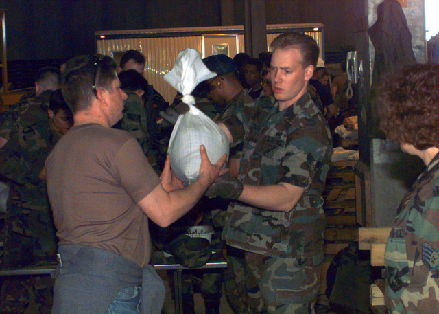 Technical Sergeant Tim Thash receives a sandbag from SENIOR AIRMAN Shawn Burson right off of the assembly line for the recent flood damage in the city of Grand Forks, 22 April 1997. They're both from the wing staff at Grand Forks AFB, North Dakota