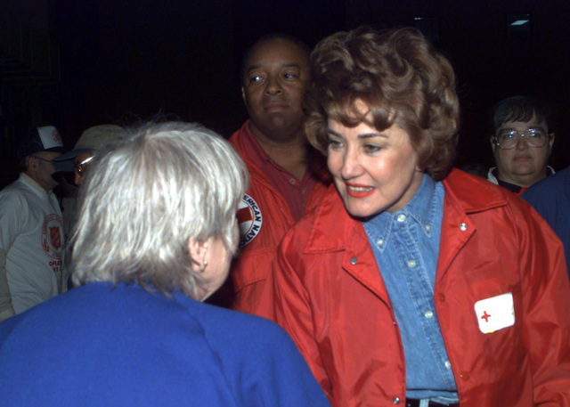 Elizabeth Dole receives a thank you from Alma Petteys, a flood victim temporarily housed at a hangar at Grand Forks AFB, North Dakota. The shelter is temporarily housing nearly 3,000 Grand Forks residents