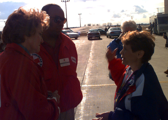Elizabeth Dole, Red Cross President, and Victor Payne, a Red Cross representative, listen to Grand Forks Mayor Pat Owens about the immediate relief some flood victims need. Shelter is being provided at Grand Forks AFB, temporarily housing nearly 3,000 Grand Forks residents